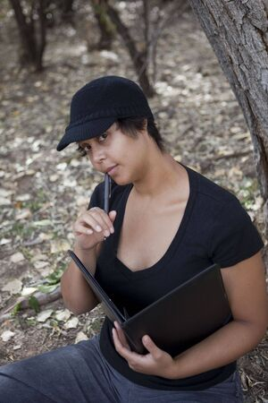 woman sitting in forest with notebook, contemplating Stock Photo - 5764352