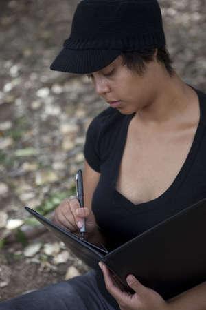 Young african american woman writing intently Stock Photo - 5764378