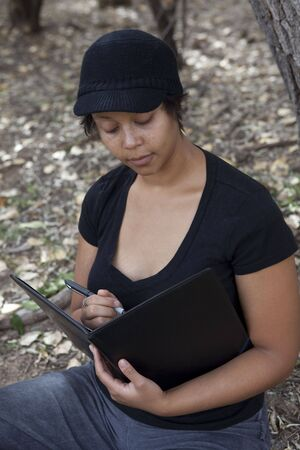 Young african-american woman sitting in forest, studying her notes Stock Photo - 5764357