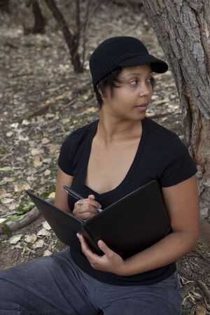 Young african-american woman sitting in forest, looking over her shoulder with notebook