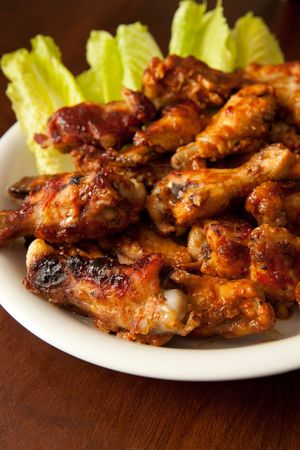 Plate of BBQ chicken wings on wood table with shallow dof
