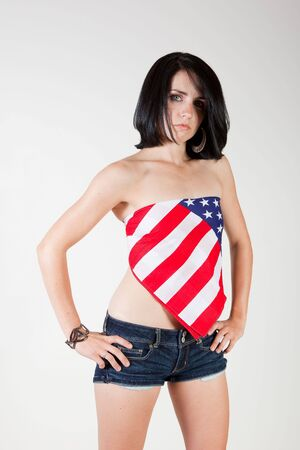 Sexy 24 year old patriotic woman posing with flag styled bandana and short jean shorts. Stock Photo