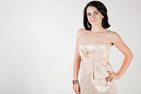 Pretty young brunette wearing champagne colored evening dress