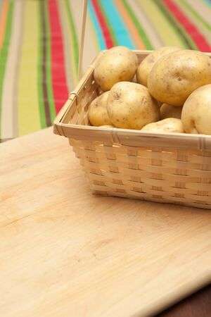 russet: basket of russet potatoes on table with colorful tablecloth Stock Photo