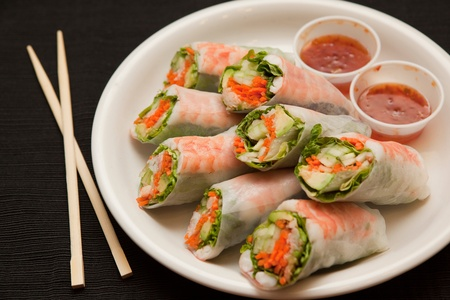 Horizontal view of shrimp spring rolls with sweet chili sauce, next to chopsticks.