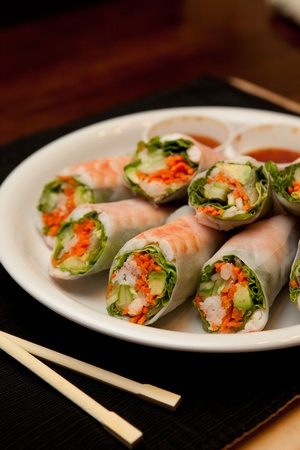 angled view: Angled view of a plate of spring rolls with sweet chili sauce; styled with chopsticks