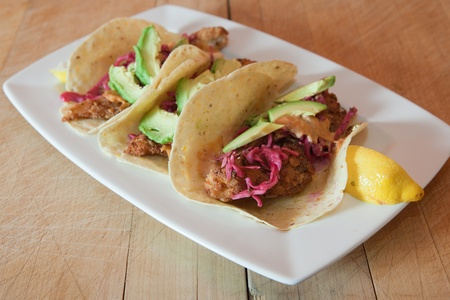 three fish tacos garnished with fresh lemon