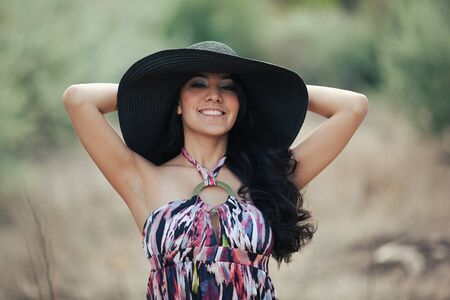 smiling pretty lady with large brimmed black straw fashionable hat outside