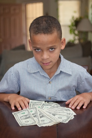 young boy sitting at table with money spread out in front of him
