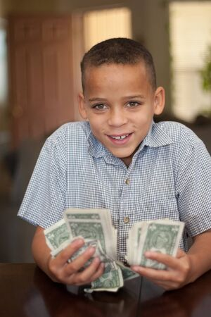 young smiling boy holding handfulls of cash Stock Photo