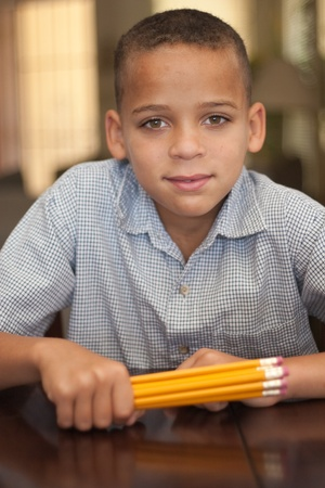 young green eyed primary school aged child holding pencils photo