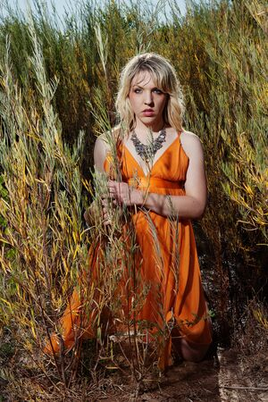 beautiful blonde woman kneeling outdoors in tall grasses photo