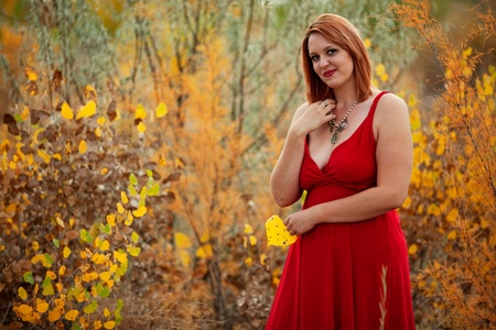 aspen leaf: young woman holding aspen leaf standing outdoors autumn Stock Photo