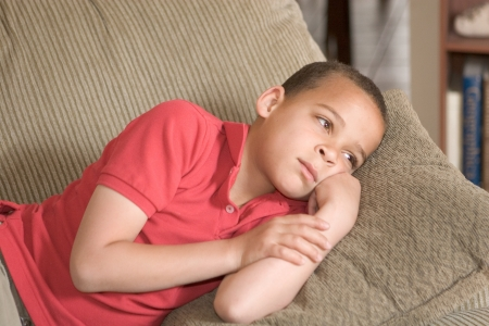 sad looking young boy resting alone on the couch Stock Photo