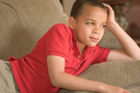 elementary school aged boy laying on couch staring into distance Stock Photo - 13644006