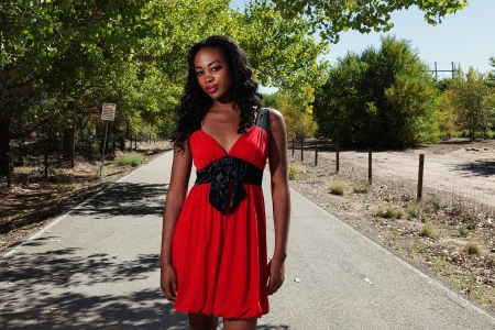 Stunning African American woman standing on a bike path in a little red dress Stock Photo