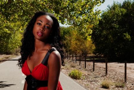 Mooie vrouw leunde naar voren buiten het dragen van een rode jurk