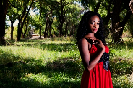 Beautiful African American woman standing outdoors in a forested area photo