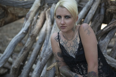 Tattoed and pierced blonde woman sitting on pile of logs outdoor in black lingerie Stock Photo