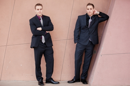 Handsome young businessmen leaning against a wall Stock Photo