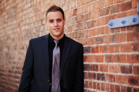 blazer: Professional man leaning against a brick wall outdoors Stock Photo