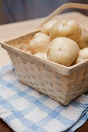 Golden potatoes in a basket on a blue and white towel
