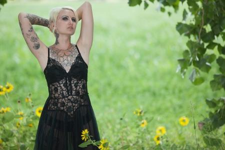 tattoed: Mujer de pie en tatuados intenso campo de flores