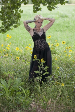 Young blonde woman holding her head, while looking frustrated  She is standing outside wearing lingerie in a field with yellow flowers   photo
