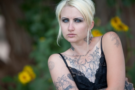 tattoos: Horizontal orientation portrait of blonde haired, blue eyed young woman covered with piercings and tattoos