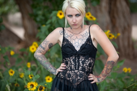 Blonde hair blue eyed punk gothic chick covered with tattoos standing in field of yellow flowers Stock Photo