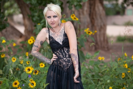 Intense alternative lifestyle punk woman in field of flowers Stock Photo