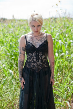 Creepy blonde haired woman standing in corn field wearing black lace lingerie
