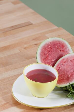 Colorful bowl of chilled watermelon soup garnished with watermelon and tarragon