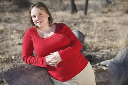 8 months pregnancy: Young 8 months pregnant young woman standing next to a log outdoors wearing a red shirt