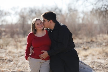 8 months pregnancy: Cute happy young pregnant married couple outdoors leaning against a log