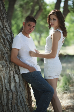 Handsome couple standing outdoors in the park looking towards the camera