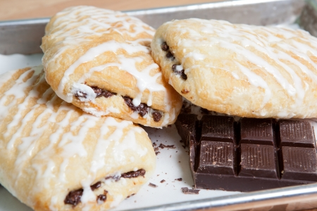Iced chocolate croissants garnished with chocolate squares on baking pan
