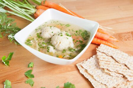 kneidl: Matzah Ball Soup with carrots and Matzo bread Stock Photo