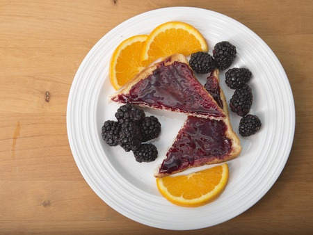 rutaceae: Plate of sliced toast with preserves, fresh blackberries and sliced navel oranges Stock Photo