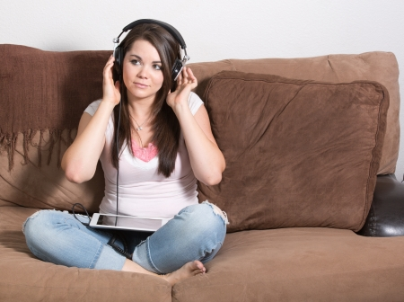 Brunette woman on large headphones and mobile tablet