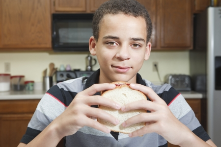 teenage mixed race boy ready to eat peanut butter and jelly sandwich in kitchen at home Stock Photo