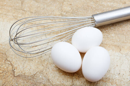 wire whisk: Wire whisk with three eggs on marble counter top