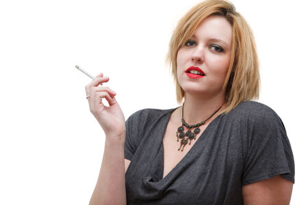 Sultry redhead woman holding slim white cigarette photo