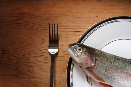 A trout on a plate with a fork. photo