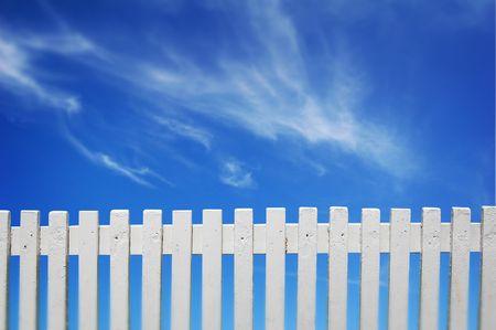 cerca blanca: Una valla de blanco y azul cielo.  Foto de archivo