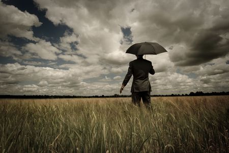 Business concept with a man holding an umbrella as a storm approaches.