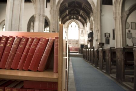 hymn: Inside a church with a shelf of hymn books. Stock Photo