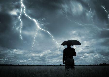 temp�te: Un homme d'affaires de la tenue d'un parapluie dans une temp�te.