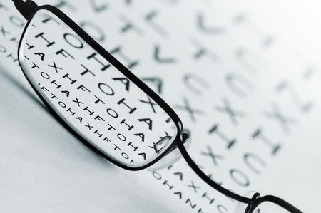 Spectacles bringing an eye test chart into focus. photo