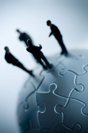A macro shot of a globe puzzle with a team of business people. photo